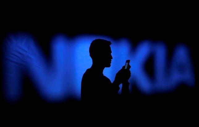 7月5日、フィンランドの通信大手ノキアと中国のスマートフォン・家電メーカー小米科技(シャオミ)は、特許のライセンス契約で合意したと発表。写真はノキアのロゴと携帯を見る男性。ボスニアで2014年撮影(2017年 ロイター/Dado Ruvic)