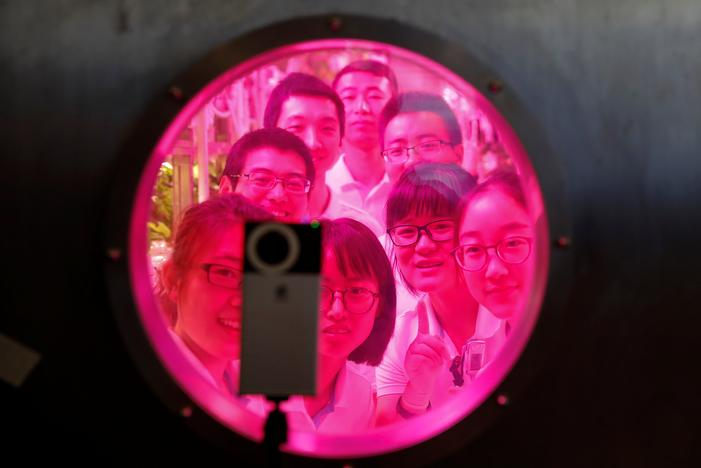 Volunteers smile to a camera from inside a simulated space cabin in which they temporarily live as a part of a scientistic Lunar Palace 365 Project, at Beihang University in Beijing, China July 9, 2017. Damir Sagolj