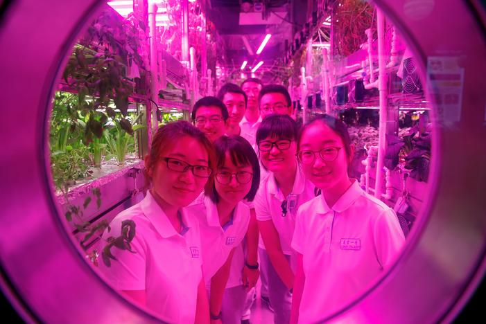 Volunteers smile from inside a simulated space cabin in which they temporarily live as a part of the scientistic Lunar Palace 365 Project, at Beihang University in Beijing, China July 9, 2017. Damir Sagolj