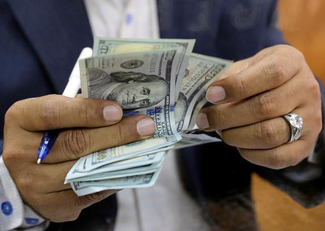7月13日、ニューヨーク外為市場では、ドルが小幅高。朝方発表された強い内容の米経済指標がドルの支援材料となったが、上値が重い展開だった。写真はドル紙幣を数える男性、カイロで3月撮影(2017年 ロイター//Mohamed Abd El Ghany)