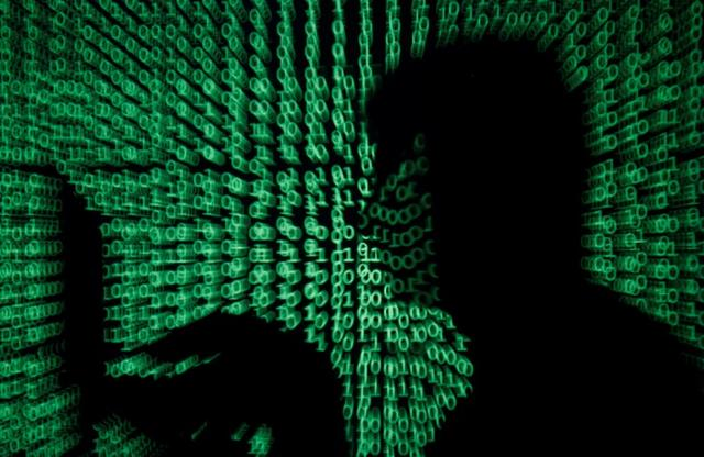 FILE PHOTO: A man holds a laptop computer as cyber code is projected on him in this illustration picture taken on May 13, 2017. REUTERS/Kacper Pempel/Illustration/File Photo