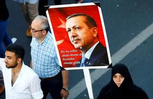 A woman holds a portrait of Turkey's President Tayyip Erdogan during a...