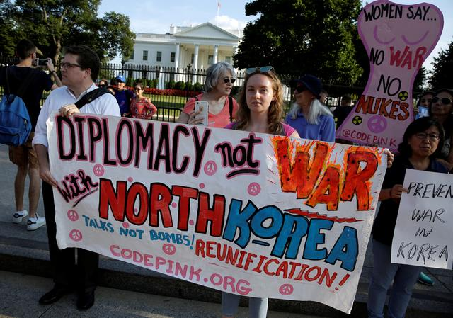 Protesters call for peaceful negotiations with North Korea during a vigil in front of the White House in Washington, U.S., August 9, 2017.   REUTERS/Joshua Roberts
