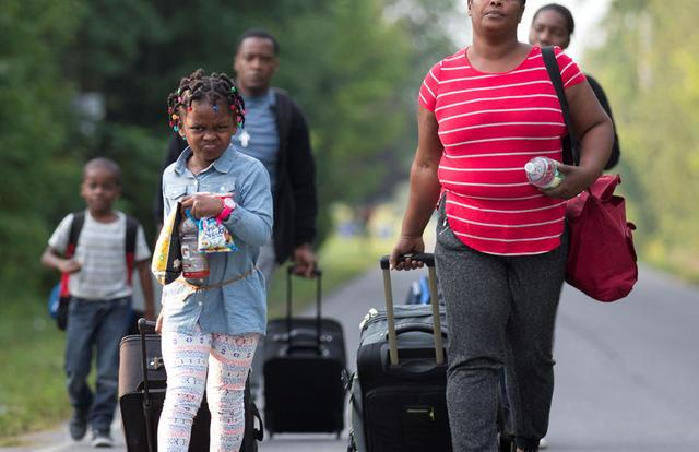 A family that stated they are from Haiti walk to the US-Canada border to cross into Canada from Champlain, New York, U.S. August 11, 2017. REUTERS/Christinne Muschi