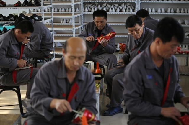 FILE PHOTO - North Korean workers make soccer shoes inside a temporary factory at a rural village on the edge of Dandong, Liaoning province, China, October 24, 2012.      REUTERS/Aly Song/File Photo