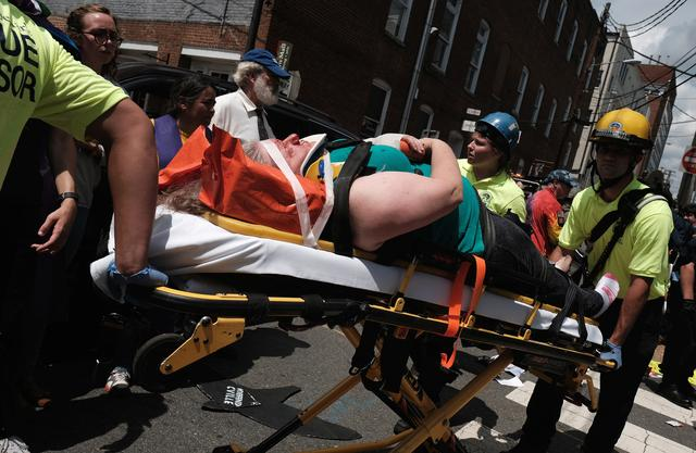Rescue workers transport a victim who was injured when a car drove through a group of counter protesters at the ''Unite the Right'' rally Charlottesville. REUTERS/Justin Ide