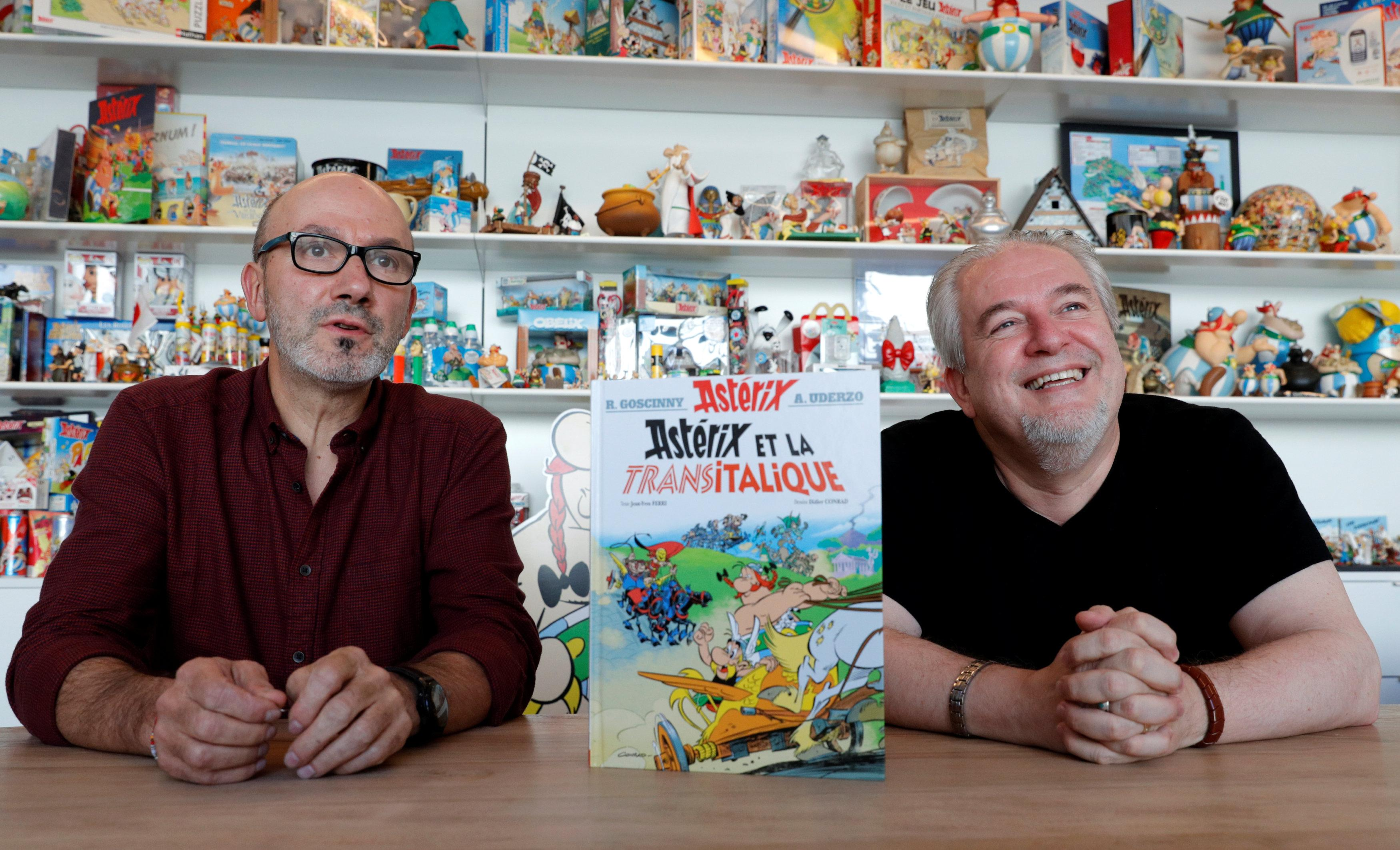 Author Jean-Yves Ferri (L) and illustrator Didier Conrad (R) stand next to a copy of their new comic album