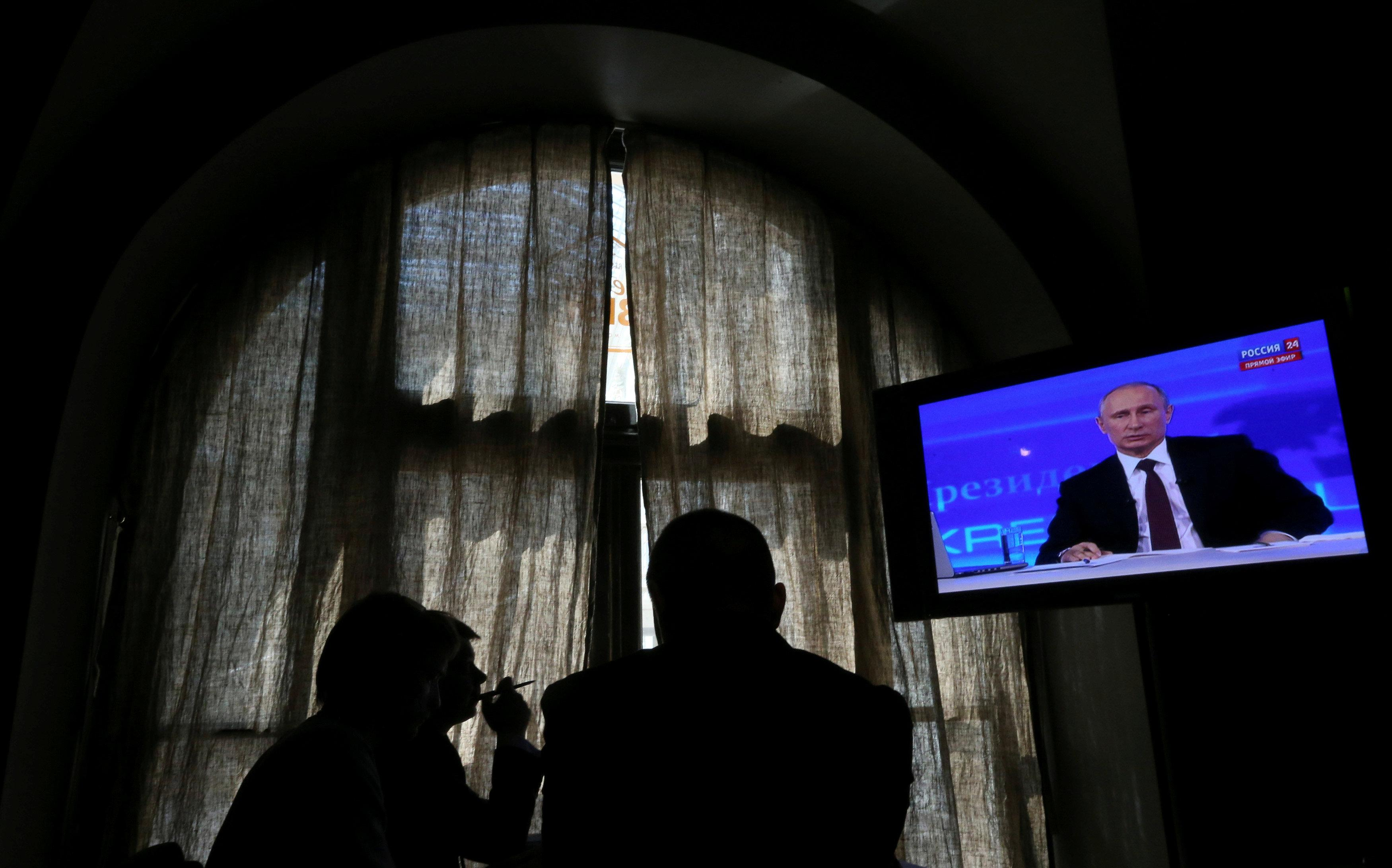 People look at a screen at a media centre during Russian President Vladimir Putin's live broadcast nationwide phone-in in Moscow, Russia April 17, 2014. Sergei Karpukhin