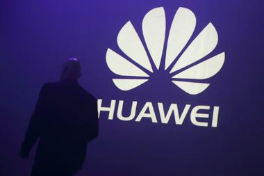 FILE PHOTO - A man walks past a logo during the presentation the Huawei's...