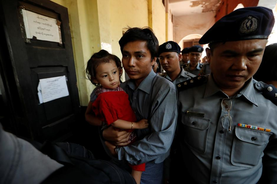 b483781e1013 Detained Reuters journalist Kyaw Soe Oo carries his daughter Moe Thin Wai  Zin while being escorted by police during a break at a court hearing in  Yangon