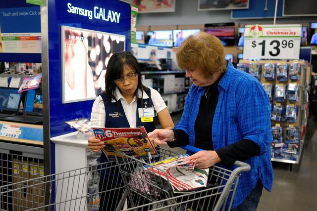 FILE PHOTO: A Walmart employee helps a customer navigate a flyer at the store in Broomfield, Colorado November 28, 2014.  REUTERS/Rick Wilking/File Photo