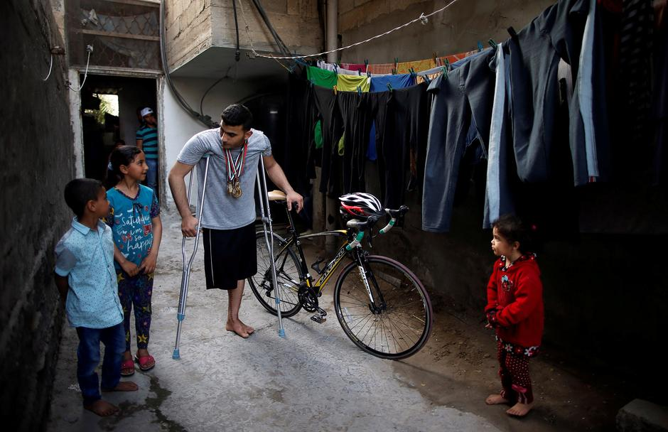 Palestinian Cyclist Alaa Al Daly  Who Lost His Leg By A Bullet Fired By Israeli Troops Talks With His Sister While Holding His Bicycle At His House In
