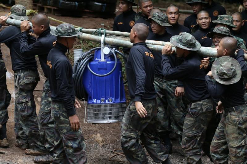 Military personnel carry a water pump machine as they enter the Tham Luang cave complex, where 12 boys and their soccer coach are trapped, in the northern province of Chiang Rai, Thailand, July 6, 2018. Athit Perawongmetha