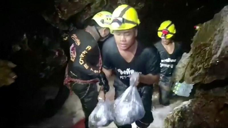 Rescuers carry supplies into the Tham Luang cave complex, where 12 boys and their soccer coach are trapped, in the northern province of Chiang Rai, Thailand, July 5, 2018. Video taken July 5, 2018.   Mandatory credit RUAMKATANYU FOUNDATION/Handout via Reuters TV