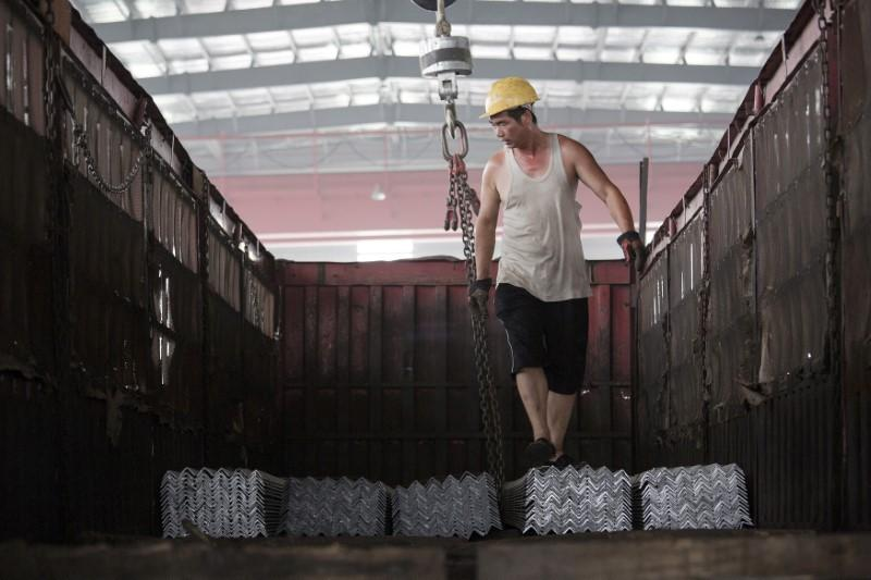 A worker helps load steel bars onto a truck at warehouse of the Baifeng Iron and Steel Corporation in Tangshan, Hebei province, China August 3, 2015. Damir Sagolj