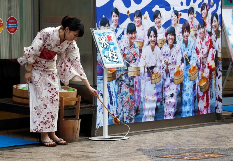 A woman wearing a Yukata, or summer kimono, splashes water onto the hot asphalt in an old Japanese tradition called Uchimizu ritual, meant to cool down the air as the water evaporates, outside a pachinko game parlor in Tokyo July 23, 2018.   Issei Kato