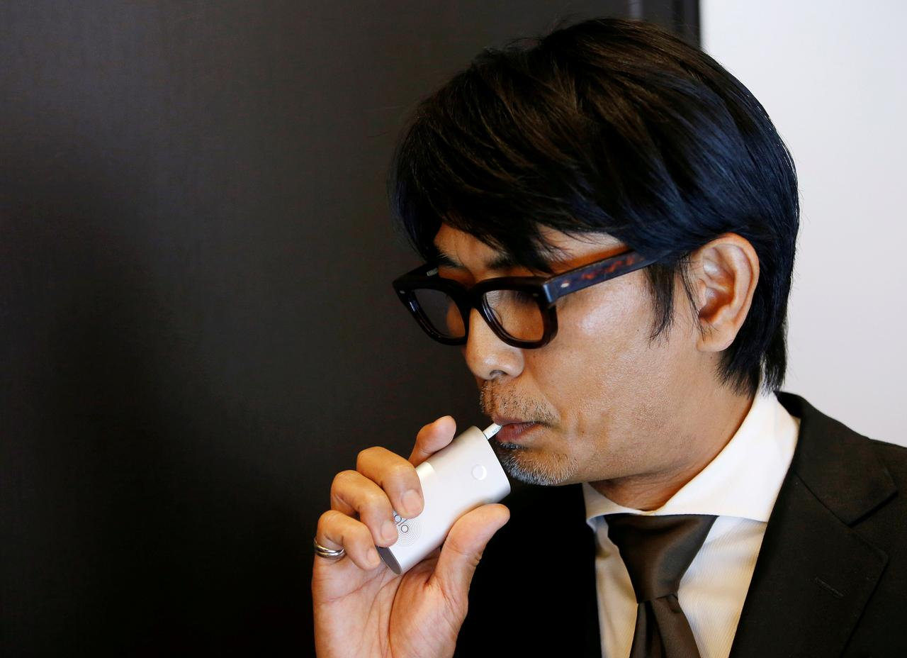 File Photo A Member Of Staff British American An Demonstrates Its New Heating System Device Glo After News Conference In Tokyo