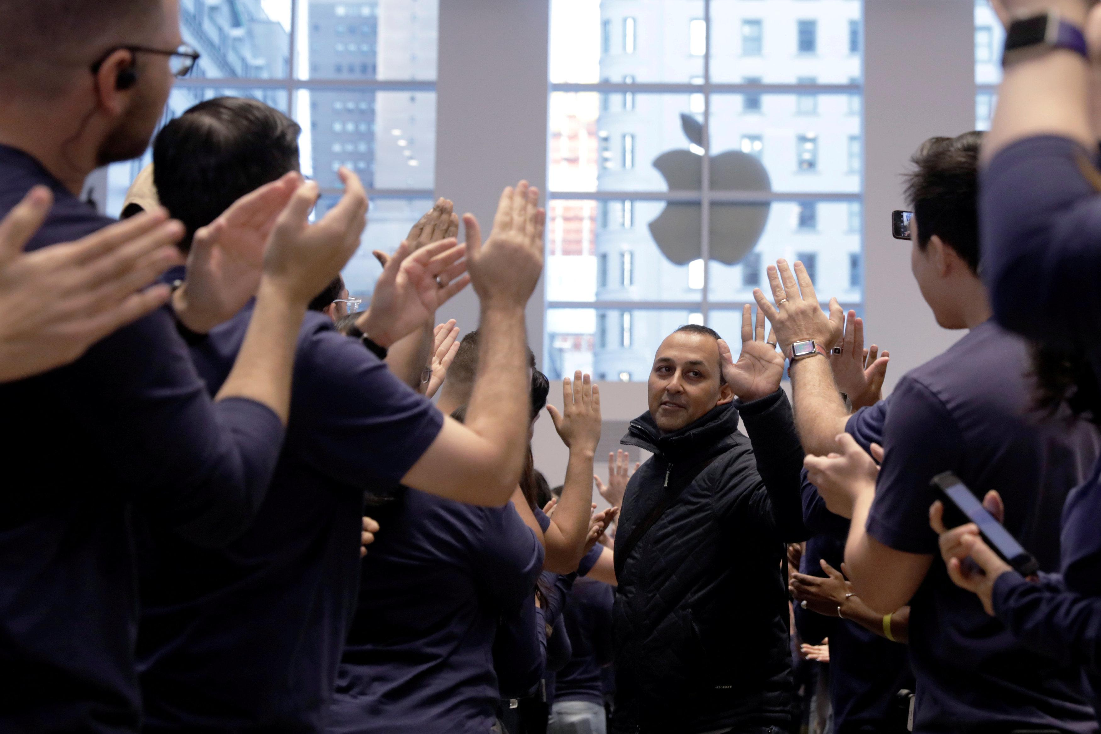 A customer is greeted by Apple employees as he enters an Apple store to purchase an iPhone X in New York, U.S., November 3, 2017.  Lucas Jackson