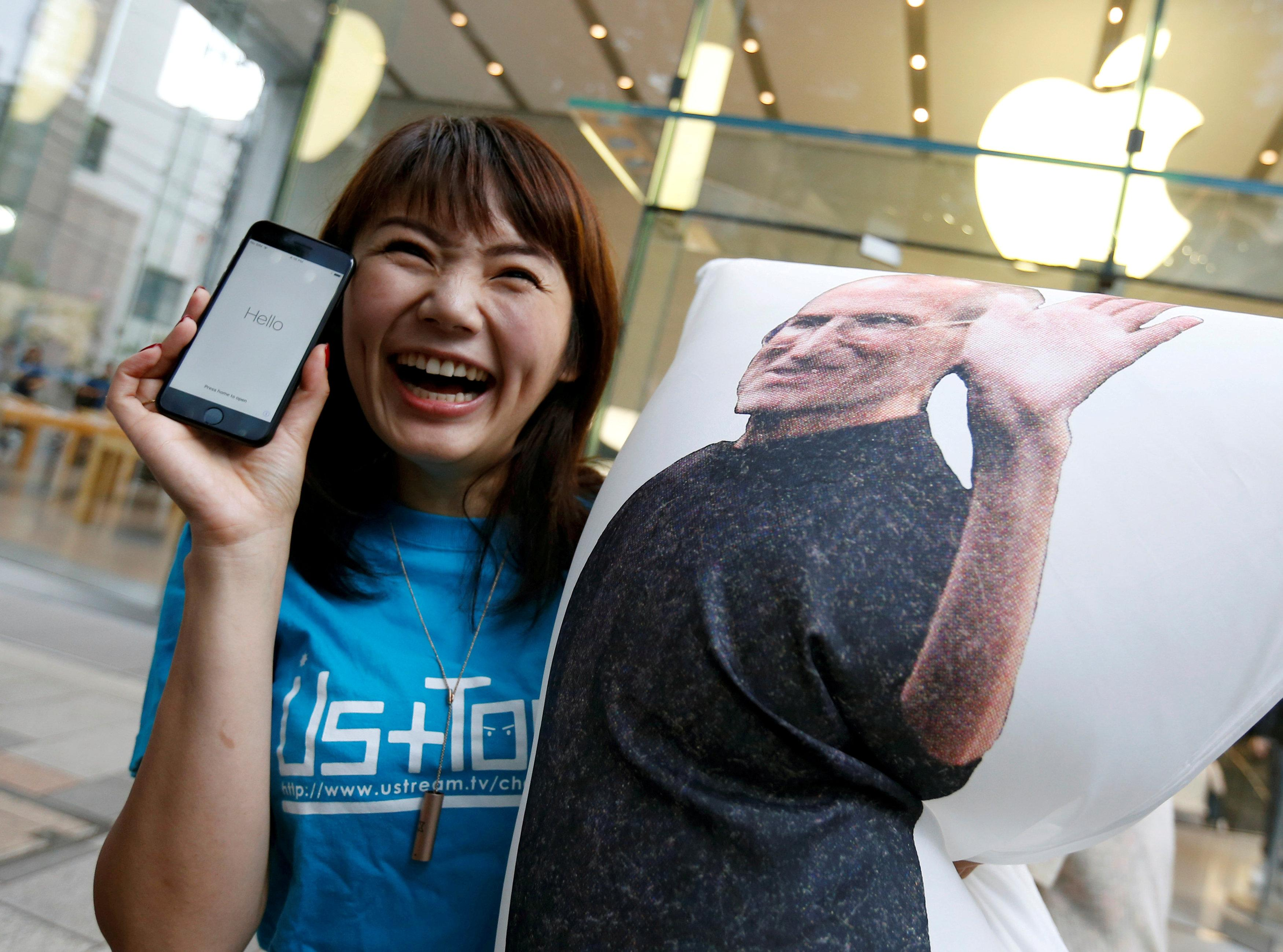 Ayano Tominaga poses with her Apple's new iPhone 7 after purchasing it at the Apple Store at Tokyo's Omotesando shopping district, Japan, September 16, 2016.    Issei Kato