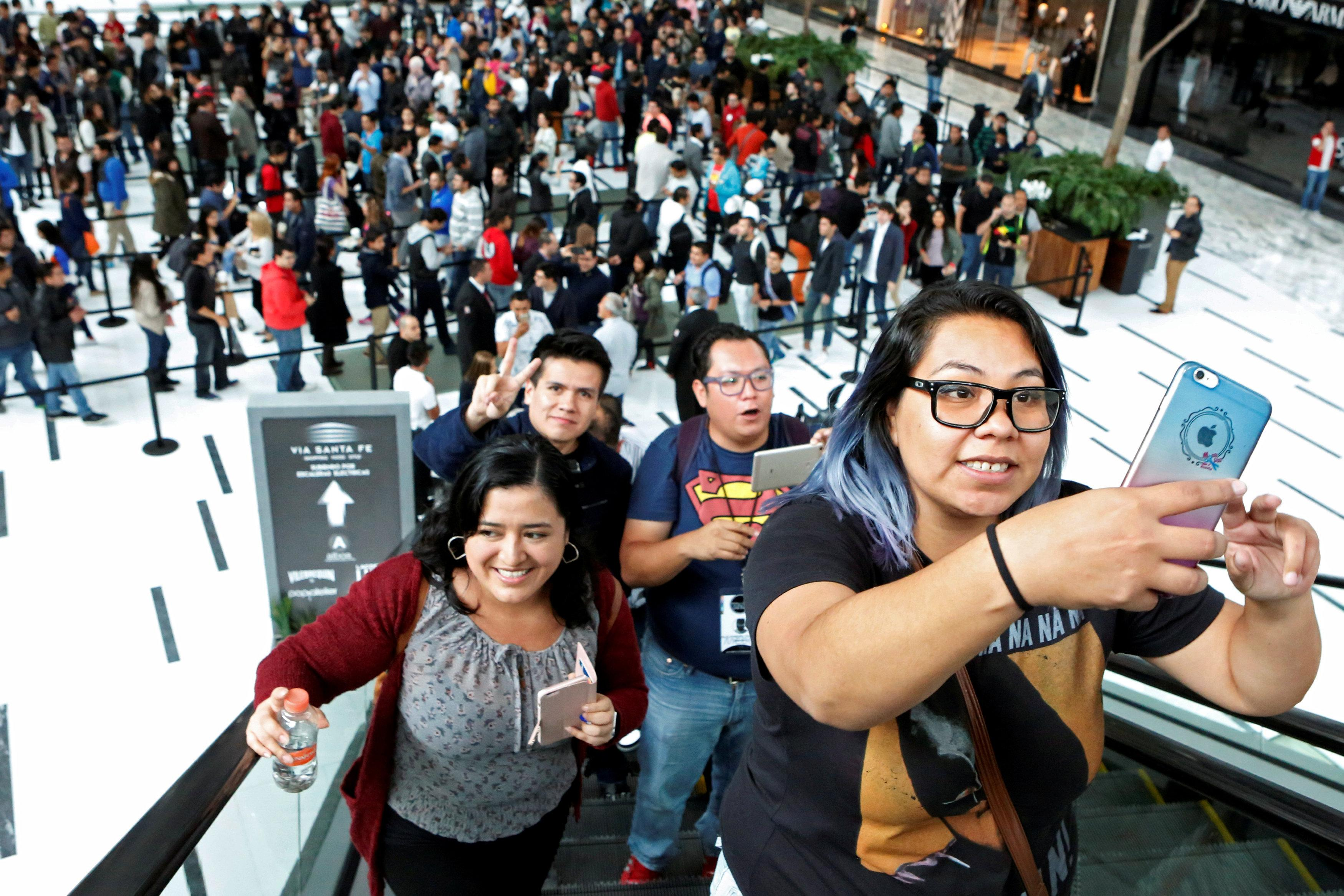 A customer takes as selfie as she waits in the queue for the opening of the first Apple Store in Mexico City, Mexico September 24, 2016.  Ginnette Riquelme