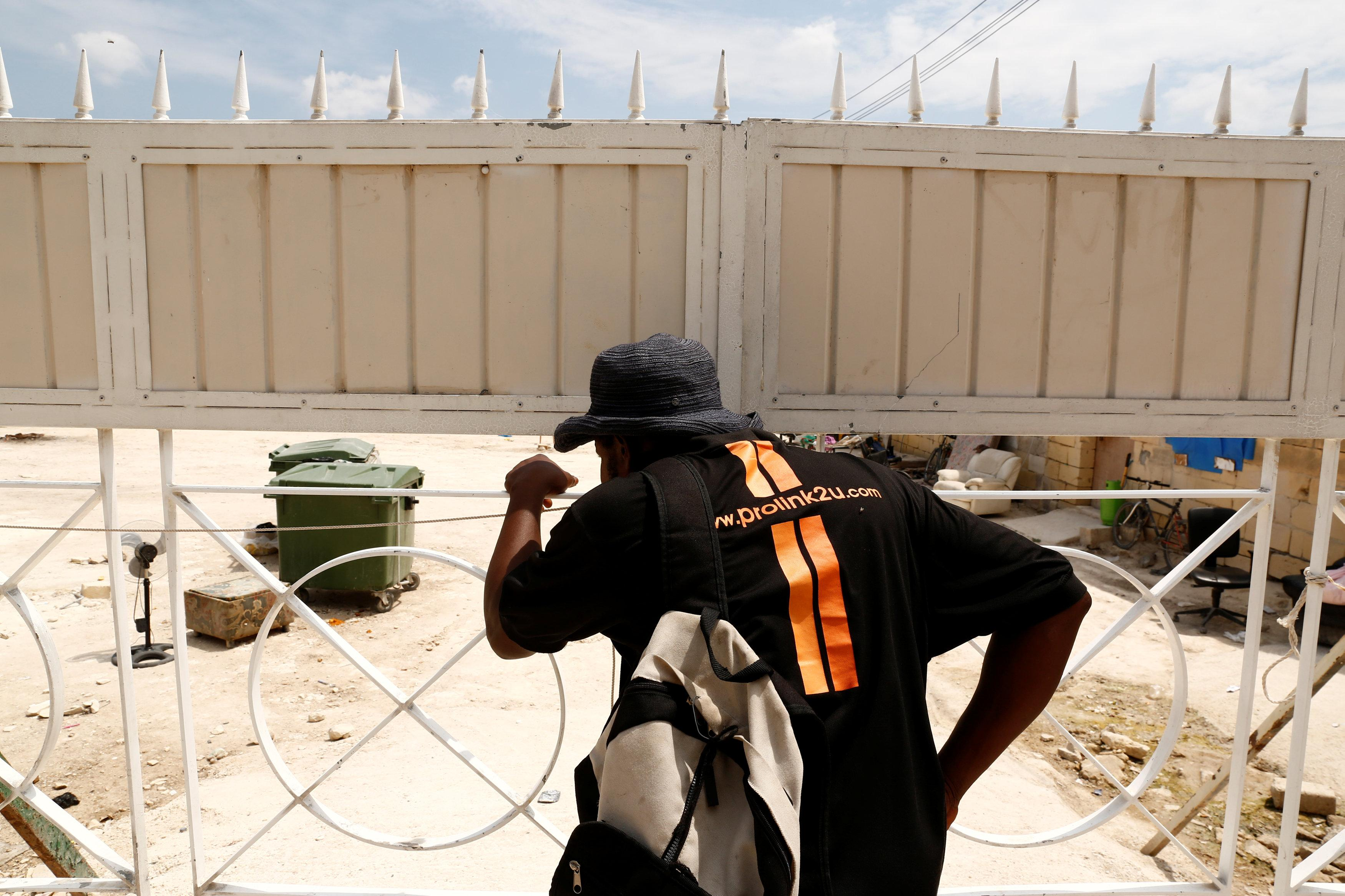 An evicted migrant looks into a farm where police evicted some 110 African migrants who had been living in stalls formerly used by cows, in Qormi, Malta August 13, 2018.  Darrin Zammit Lupi