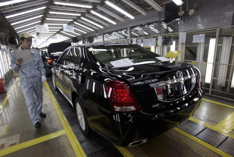An employee walks past as he checks on newly-produced cars at a Toyota factory in Tianjin, March 23, 2012. Stringer