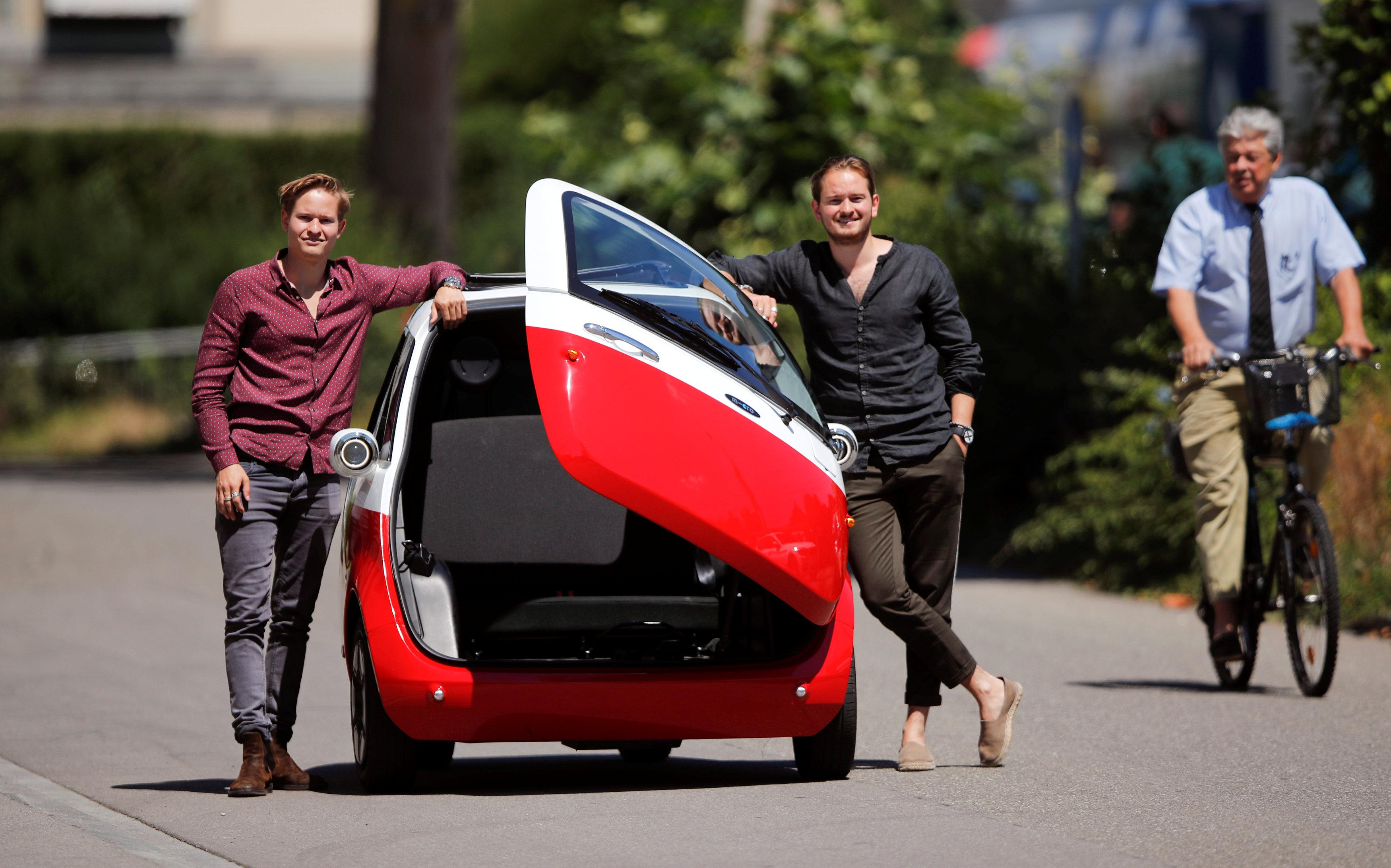 Chief Operating Officer Oliver (L) and his brother Chief Marketing Officer Merlin Ouboter of Swiss Microlino AG pose beside an electric-powered Microlino car in Kuesnacht, Switzerland July 13, 2018. Picture taken July 13, 2018.    Arnd Wiegmann