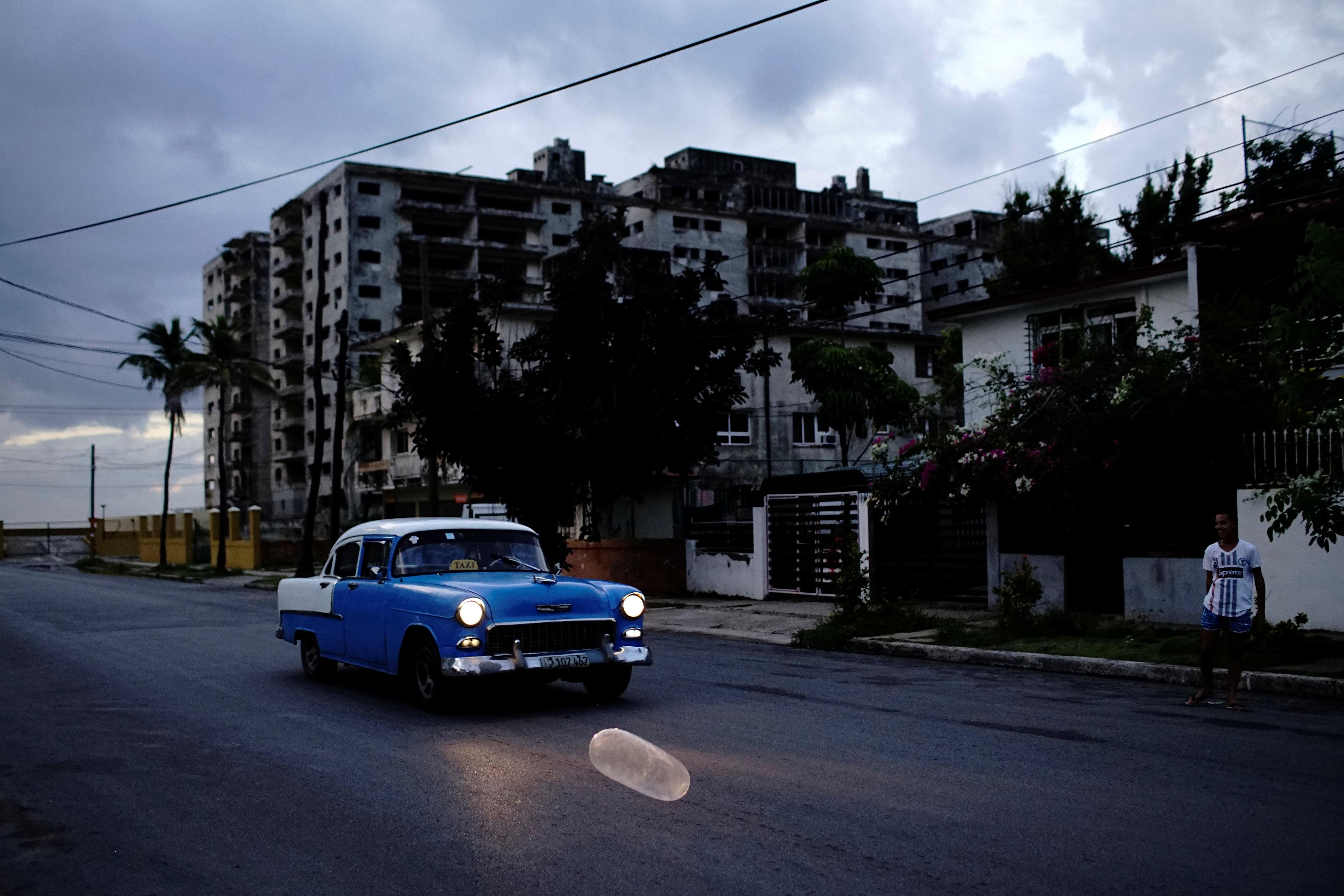 A vintage car passes by an inflated condom on the street in Havana, Cuba, August 27, 2018. Picture taken on August 27, 2018. Alexandre Meneghini