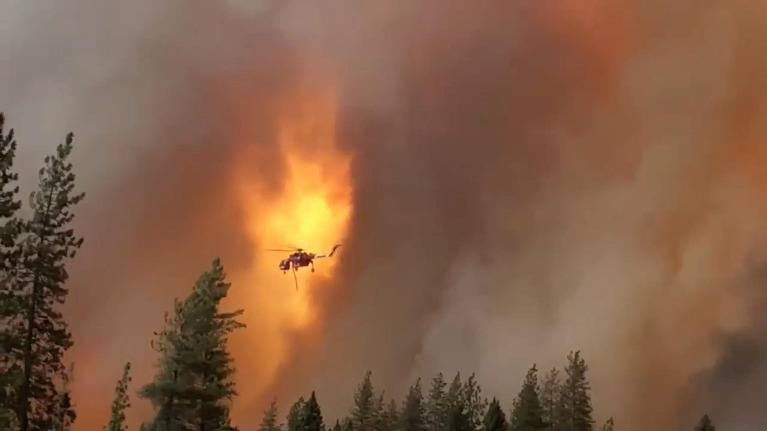 A helicopter drops water on a forest fire in Shasta County in California, U.S., September 5, 2018 in this picture obtained on September 6, 2018 from a social media video. CALIFORNIA HIGHWAY PATROL/via