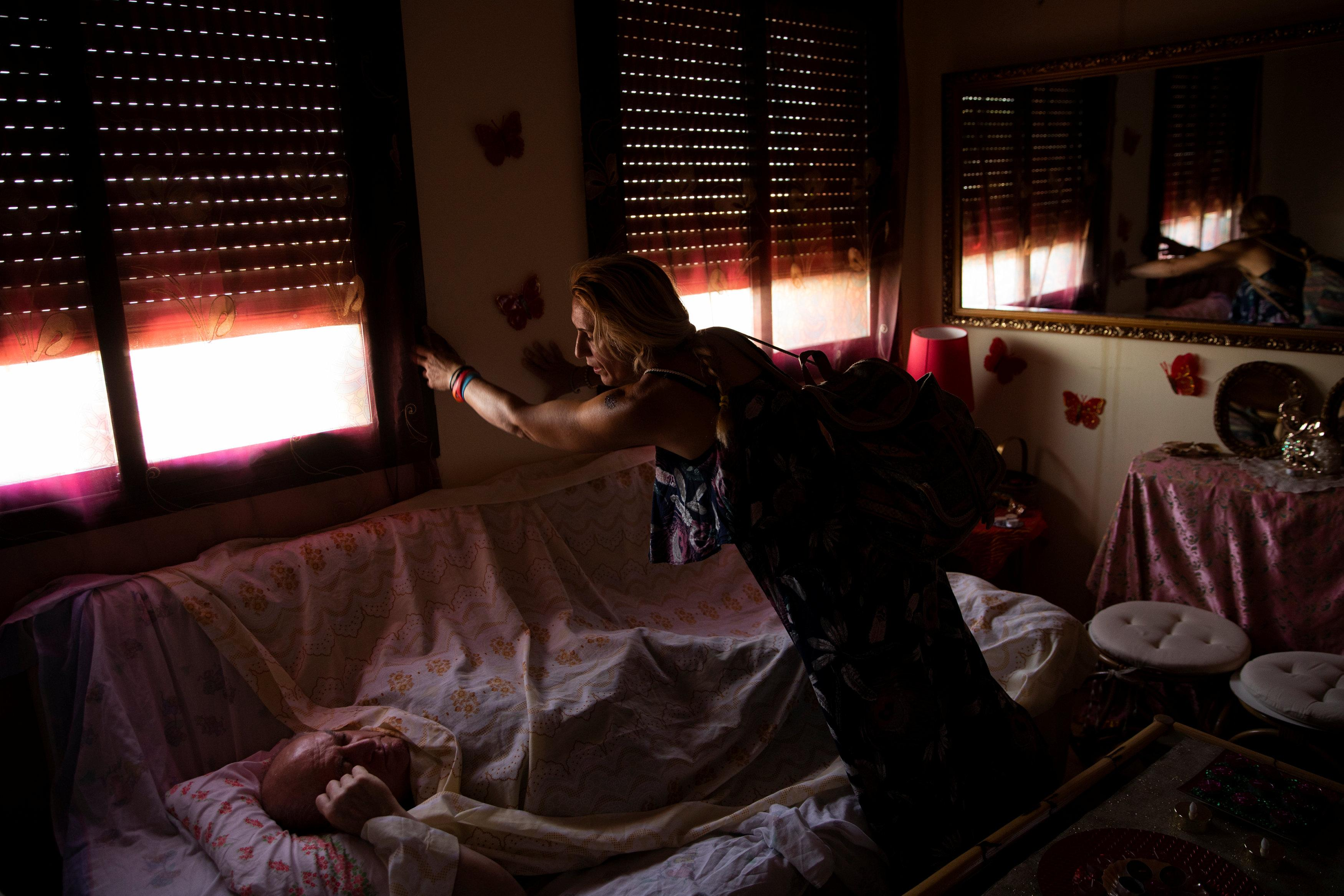 Maria Isabel Rodriguez Romero, 48, lowers the shutters so her father Efren Rodriguez Gonzalez, 74, can sleep in the living room of the home where they are squatting in a village in the province of Toledo, central Spain, August 8, 2018.  Susana Vera