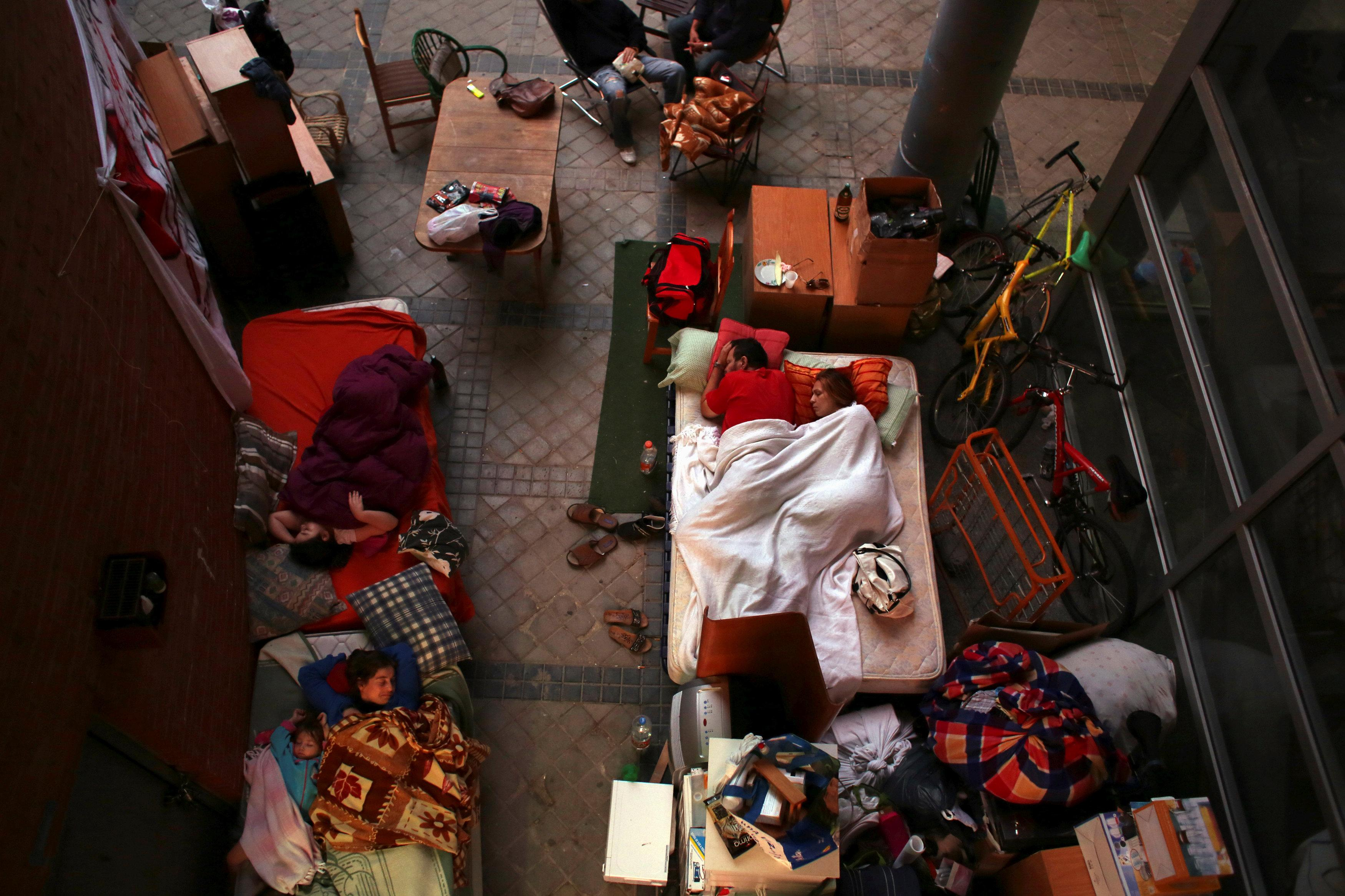 Maria Isabel Rodriguez Romero and her husband Benigno Ferrer (under white blanket) sleep next to their daughter Maria Isabel Ferrer Rodriguez, 8, (top L) outside the apartment where they were evicted from in Madrid, Spain, September 27, 2013.   Susana Vera/File photo