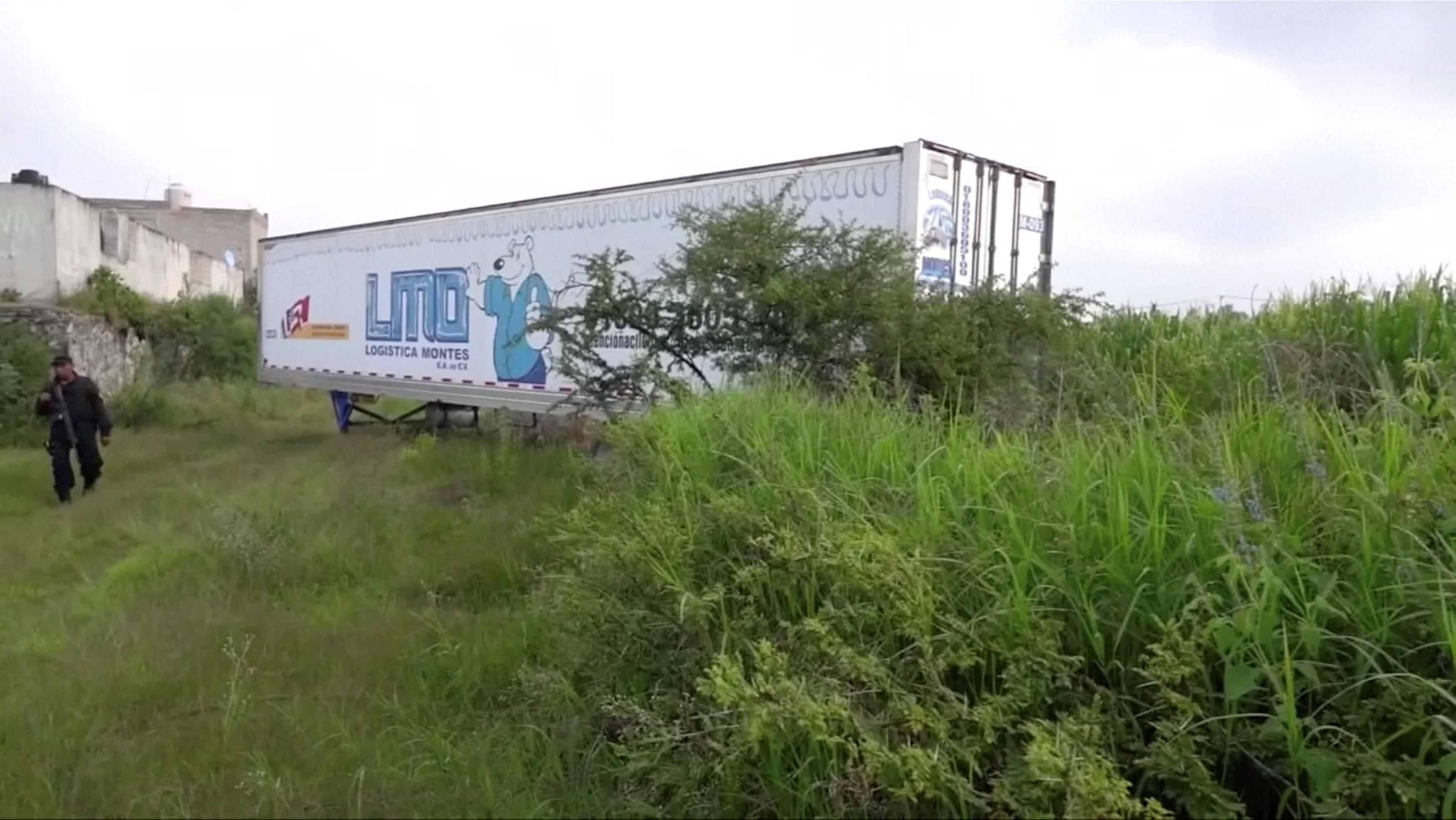 A police officer walks past an abandoned trailer full of bodies in Tlajomulco de Zuniga, Jalisco, Mexico September 15, 2018 in this still image taken from a video obtained September 17, 2018.  TV/via