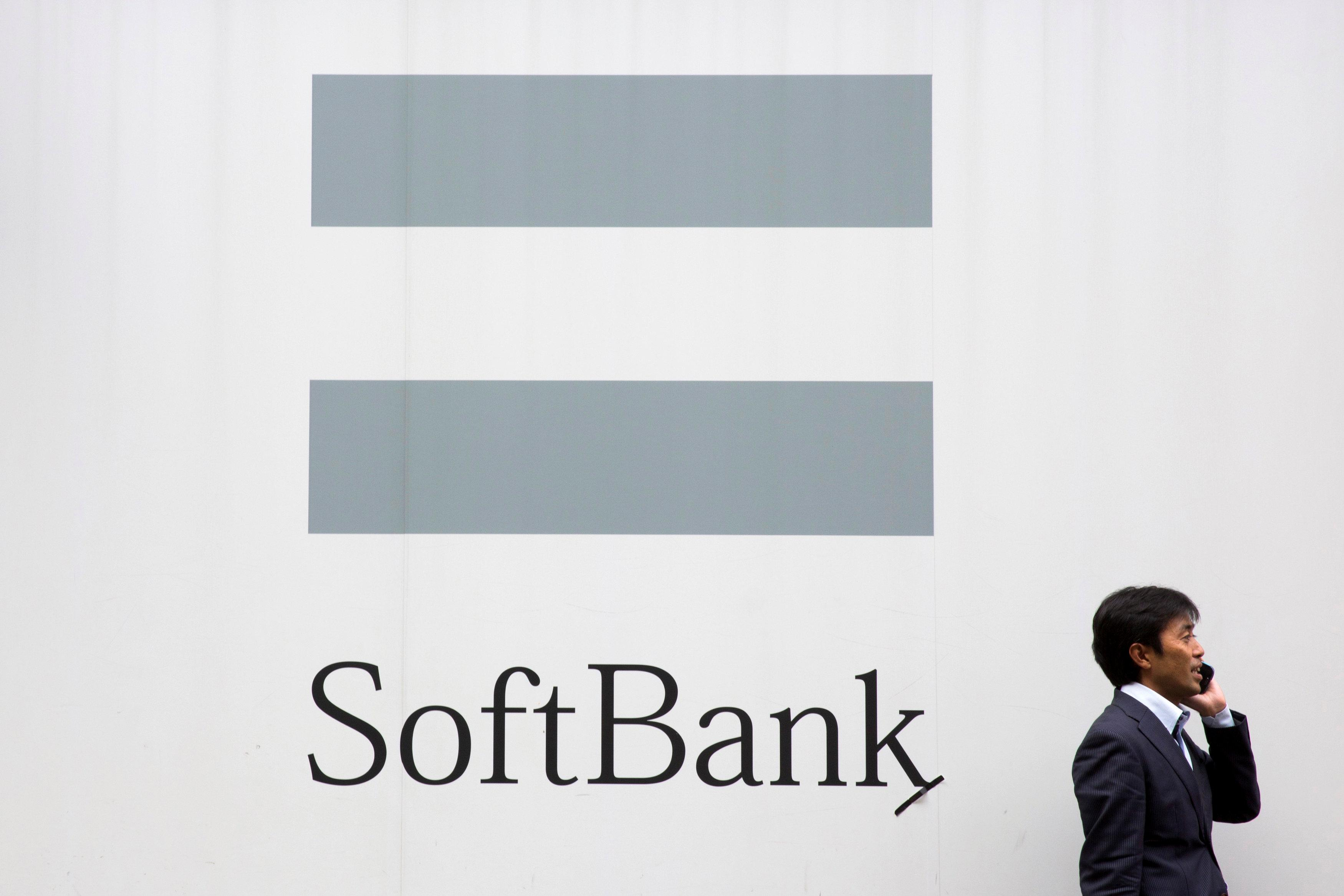 FILE PHOTO : A man talks on the phone as he stand in front of an advertising poster of the SoftBank telecommunications company in Tokyo October 16, 2015. Thomas Peter