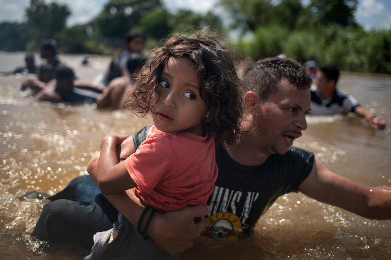 Luis Acosta holds 5-year-old Angel Jesus, both from Honduras, as a caravan of migrants from Central America en route to the United States crossed through the Suchiate River into Mexico from Guatemala in Ciudad Hidalgo, Mexico, October 29.       REUTERS/Adrees Latif