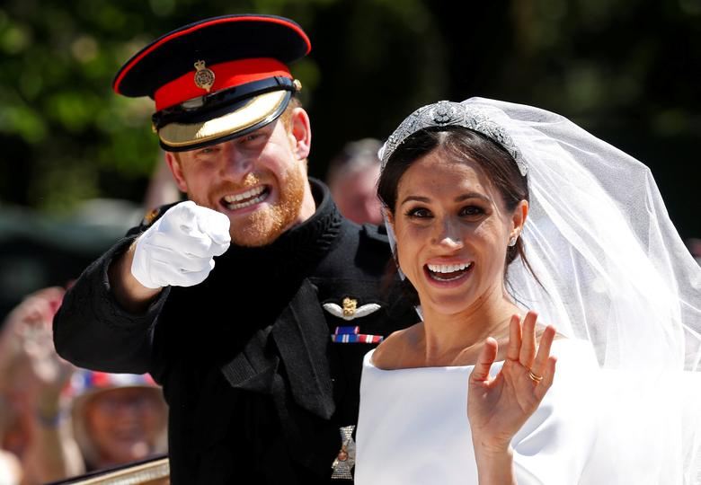 Britain's Prince Harry gestures next to his wife Meghan as they ride a horse-drawn carriage after their wedding ceremony at St George's Chapel in Windsor Castle, May 19.    REUTERS/Damir Sagolj