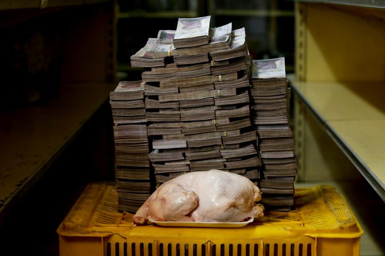 A 2.4-kg chicken is pictured next to 14,600,000 bolivars, its price and the equivalent of $2.22 USD, at a mini-market in Caracas, Venezuela, August 16. It was the going price at an informal market in the low-income neighborhood of Catia.     REUTERS/Carlos Garcia Rawlins