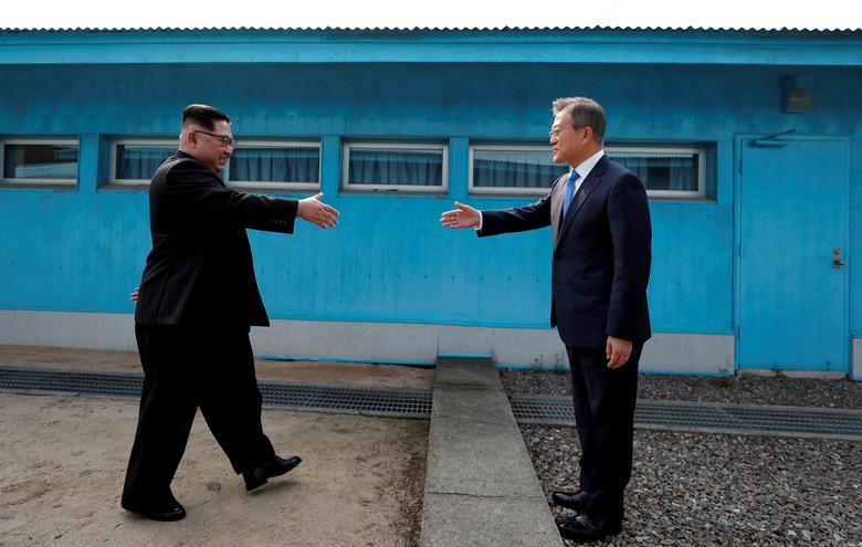 South Korean President Moon Jae-in and North Korean leader Kim Jong Un shake hands at the truce village of Panmunjom inside the demilitarized zone separating the two Koreas, South Korea, April 27.      Korea Summit Press Pool/Pool via Reuters