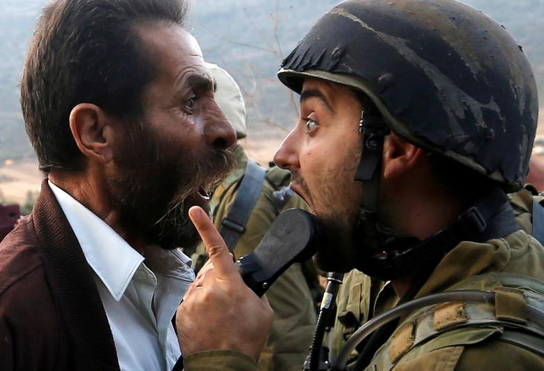 A Palestinian man argues with an Israeli soldier during clashes over an Israeli order to shut down a Palestinian school near Nablus, in the occupied West Bank, October 15.    REUTERS/Mohamad Torokman