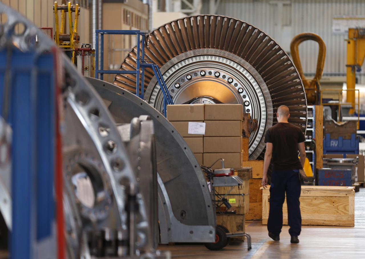a worker walks past a gas turbine under construction at the gas turbines  production unit of the general electric plant in belfort, june 24, 2014