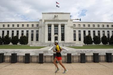 A jogger runs past the Federal Reserve building in Washington, DC