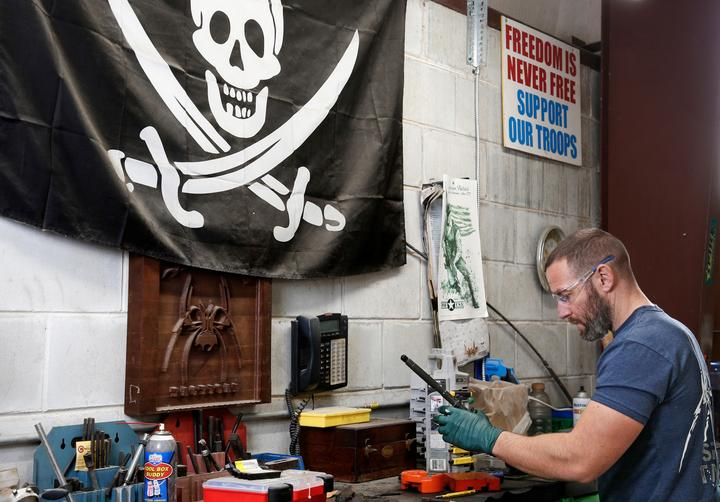 Rodger Brown finishes work on a front sight post assembly for an AR-15...