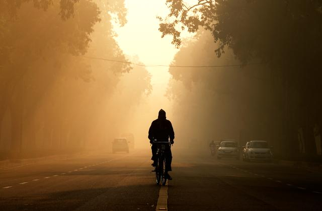 FILE PHOTO: A man rides his bicycle on a smoggy morning in New Delhi, India, December 26, 2018. REUTERS/Adnan Abidi