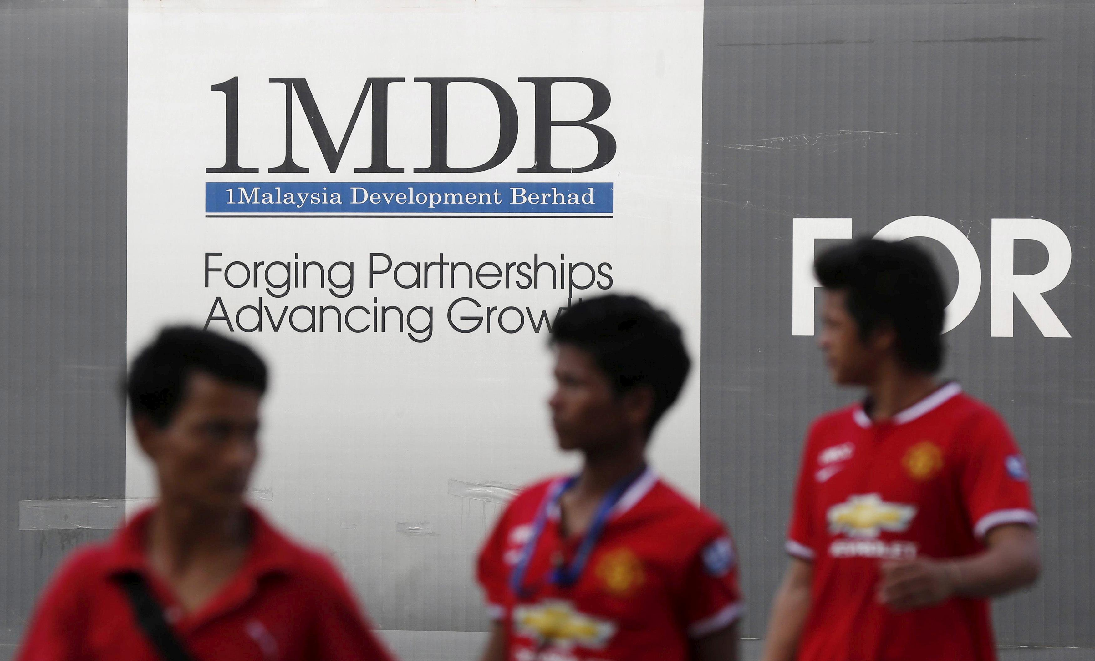 Men walk past a 1Malaysia Development Berhad (1MDB) billboard at the fund
