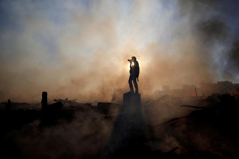 A photographer take a photos of a wildfire near the Paranoa neighborhood in Brasilia, Brazil, July 20, 2018. REUTERS/Ueslei Marcelino