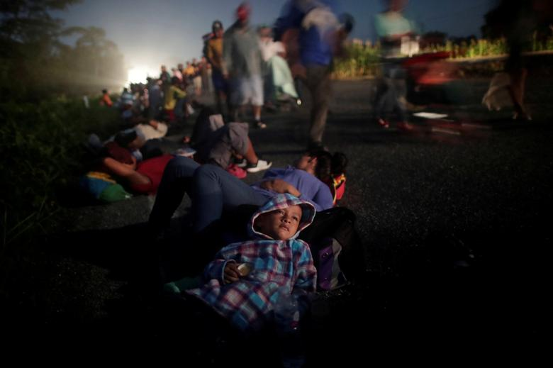 Glenda Escobar, 33, a migrant from Honduras, part of a caravan of thousands from Central America, rests on the road with her son Adonai, as they make their way to Pijijiapan from Mapastepec, Mexico, October 25, 2018. REUTERS/Ueslei Marcelino