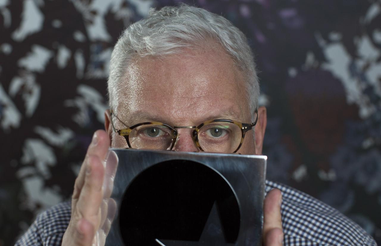 25576e063 Ted Baker CEO Ray Kelvin obscures his face as he poses for a portrait at  his company offices in London March 12