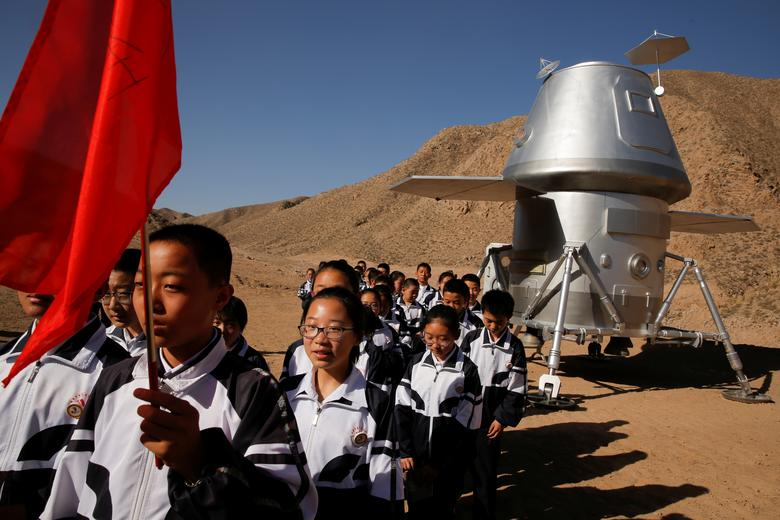 Students leave a mock space capsule after a lesson at the C-Space Project Mars simulation base in the Gobi Desert, April 17. REUTERS/Thomas Peter