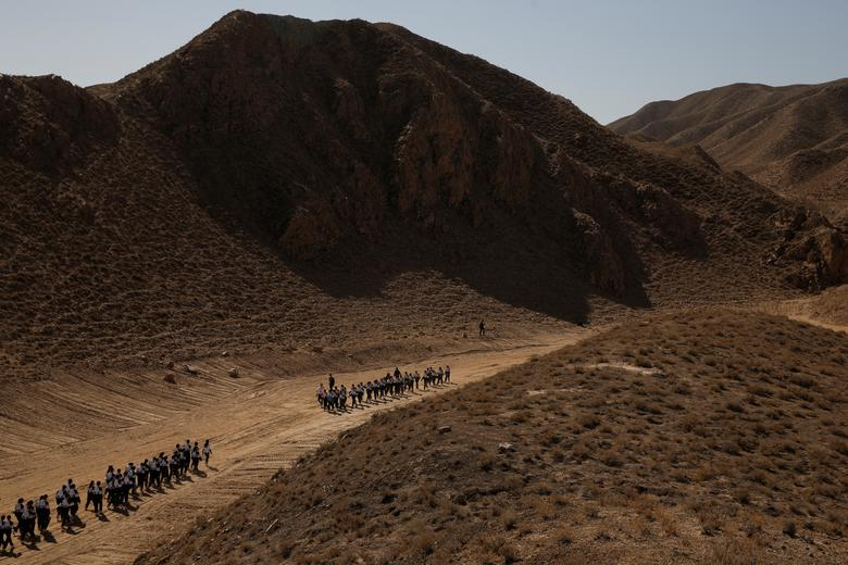Students walk through Gobi Desert near the C-Space Project Mars simulation base, April 17. REUTERS/Thomas Peter