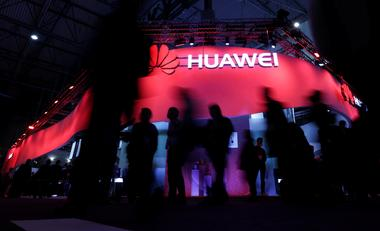 FILE PHOTO: Visitors walk past Huawei's booth during Mobile World Congress...