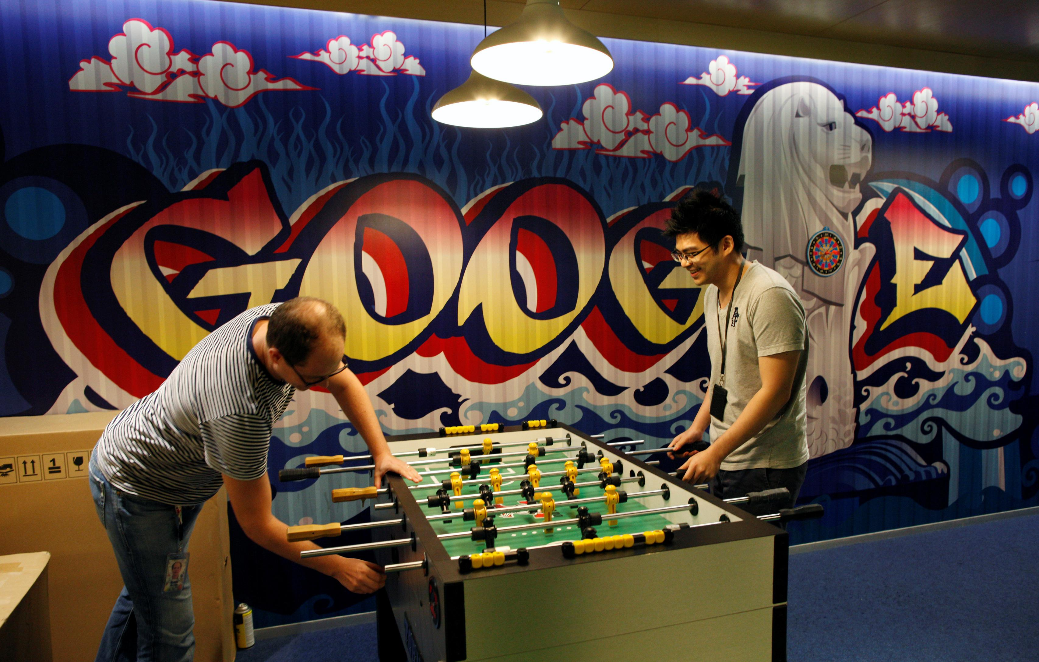 Google's communications manager Robin Moroney plays table soccer with a Google employee at a recreational area of their Singapore office, Singapore July 8, 2013. Edgar Su